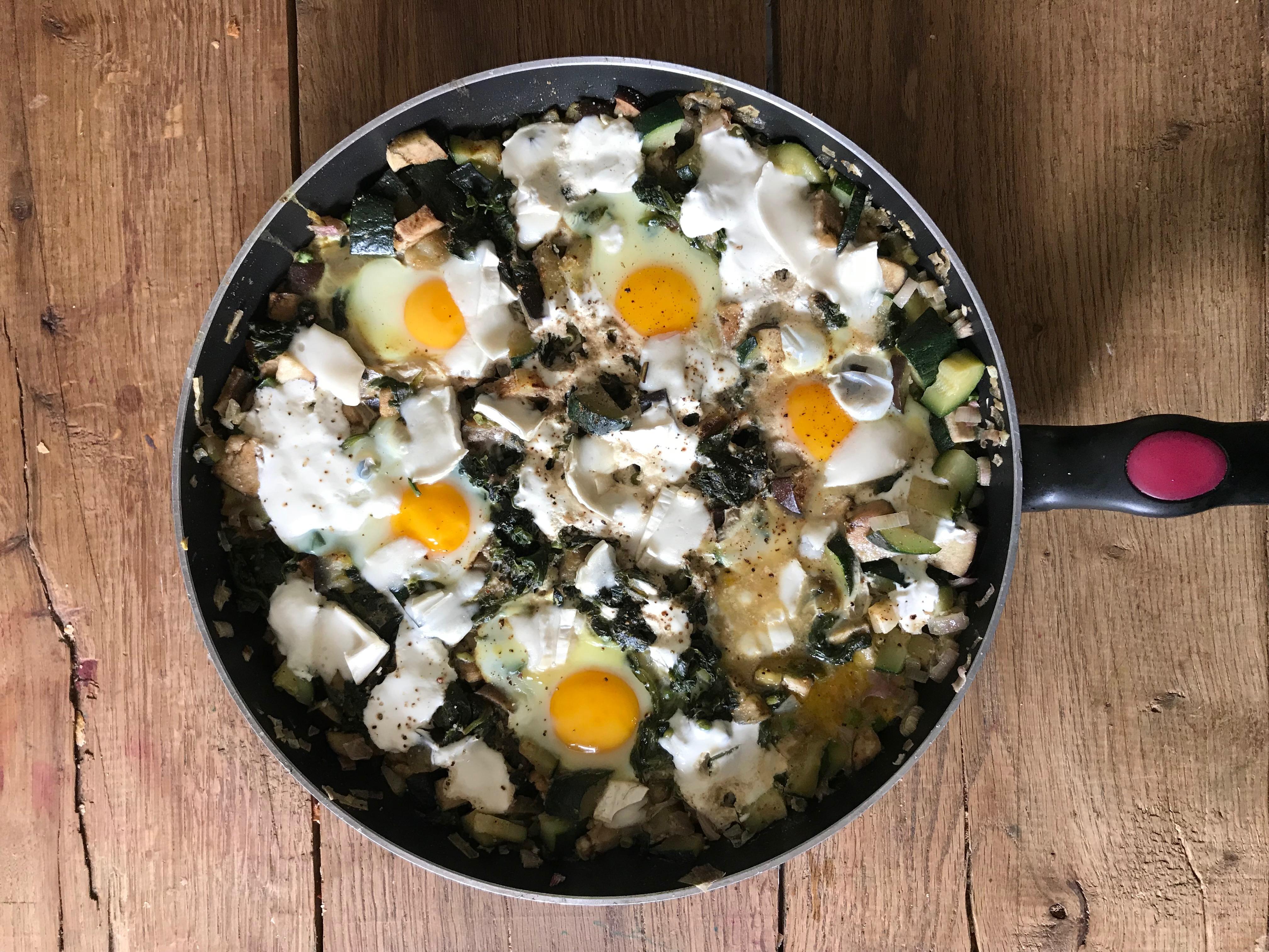 Groene shakshuka eieren gestoofd in groente